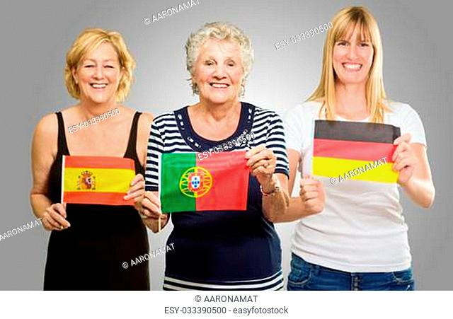 Three Woman Holding Different Flag On Gray Background
