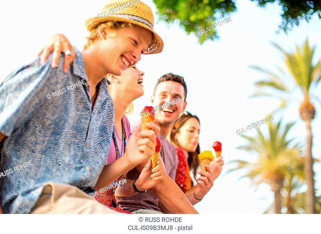 Four adult friends laughing and eating ice cream cones, Majorca, Spain