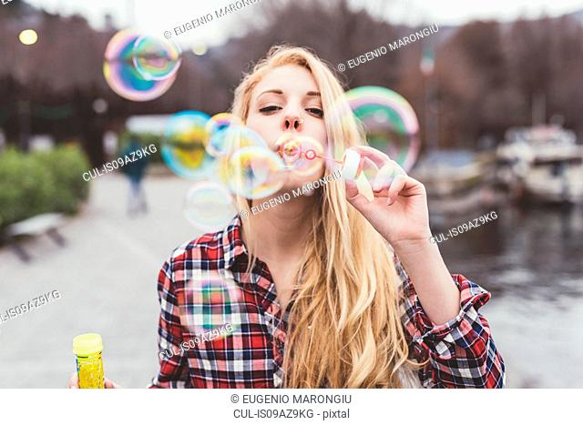 Portrait of young woman on waterfront blowing bubbles, Lake Como, Italy