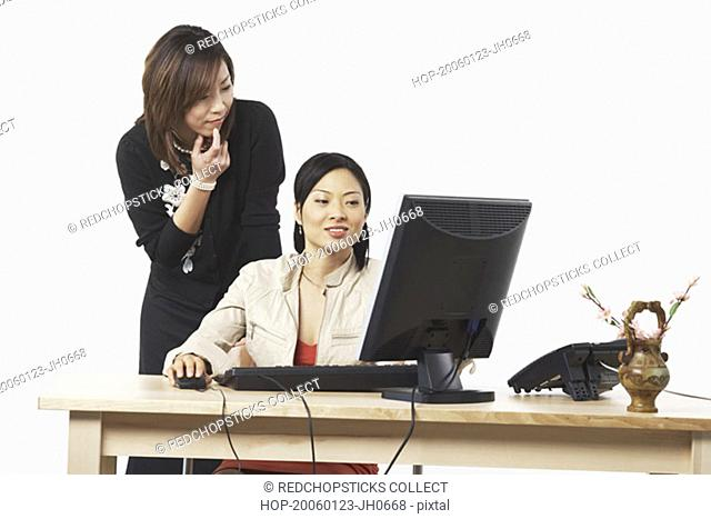 Two businesswomen looking at a computer