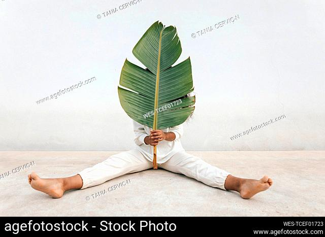 Woman covering face with big banana leaf while sitting in front of white wall