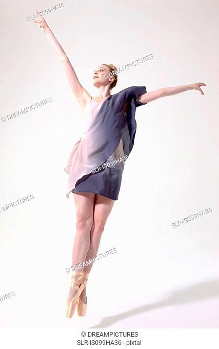 Ballerina jumping with arms raised and toes pointed