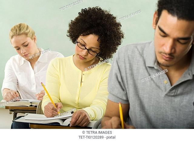 Three college students in class taking test
