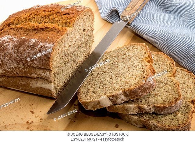sliced irish soda bread with bread knife on a wooden board