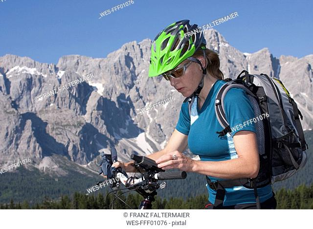 Italy, Dolomites, Female mountainbiker, side view, portrait, close-up