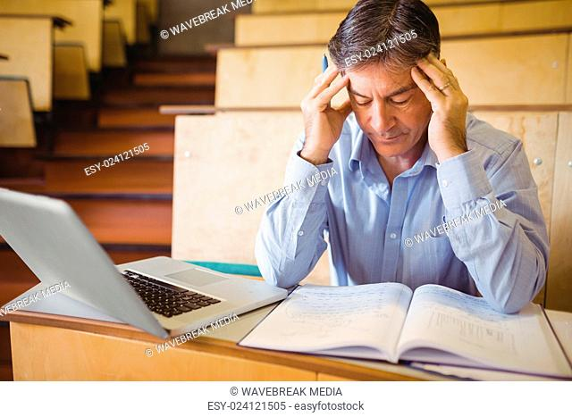 Depressed professor sitting with notes and laptop
