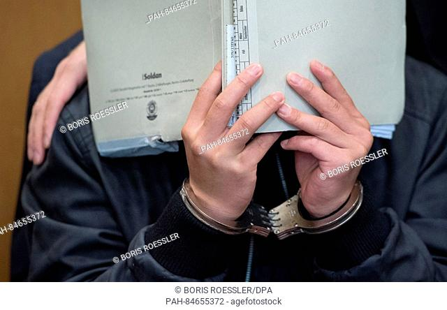 Yejun G., one of the defendants in a murder case, covers his face with a folder in Frankfurt am Main, Germany, 10 October 2016. Yejun G