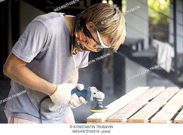 Man sanding wood with a random orbital sander