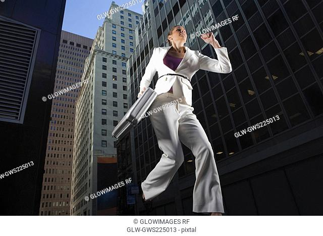 Low angle view of a businesswoman running with a briefcase