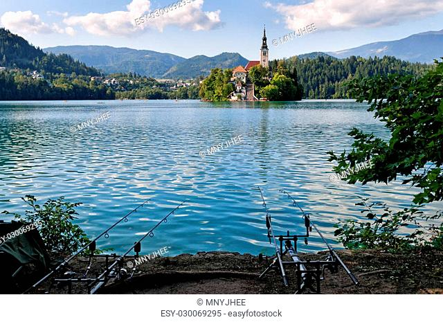 Two fishing rods on the Alpine Bled lake with view on the famous island with monastery