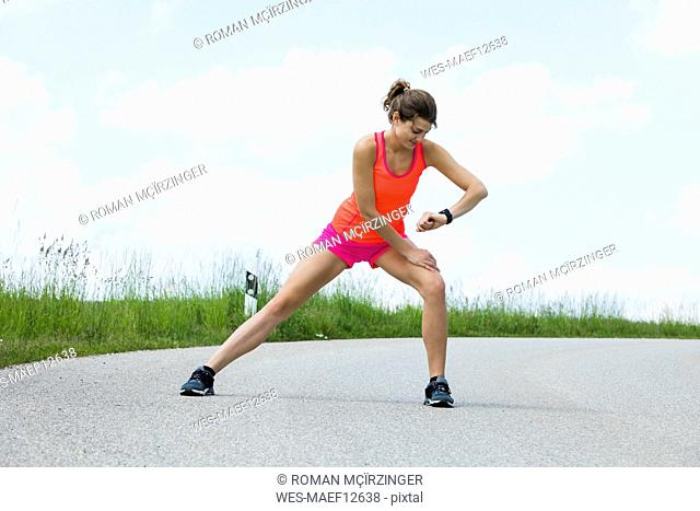 Jogging woman doing stretching exercises on street
