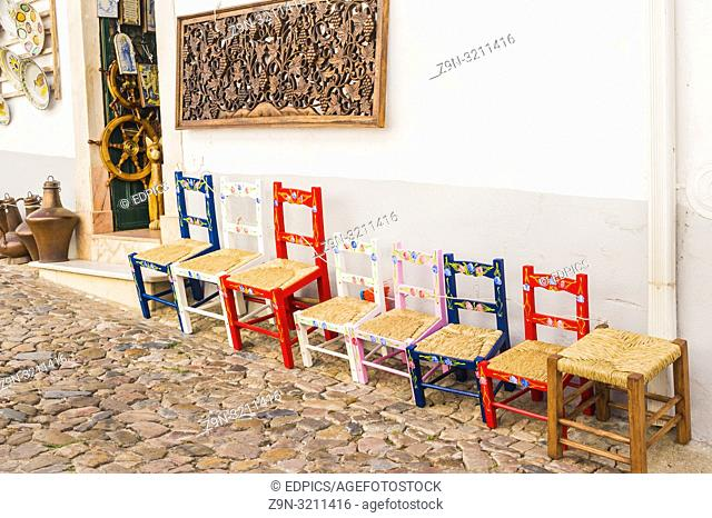 typical multicolored handcrafted chairs in front of a store selling local handicraft, estremoz, alentejo, portugal
