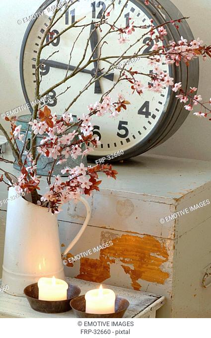 Blooming branches, candles and clock
