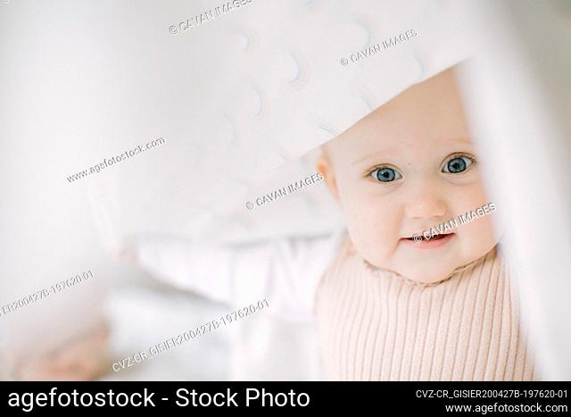 Baby girl looking at the camera while playing under a blanket