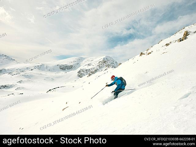 Male skier skis down a powdery slope on a sunny day in the backcountry
