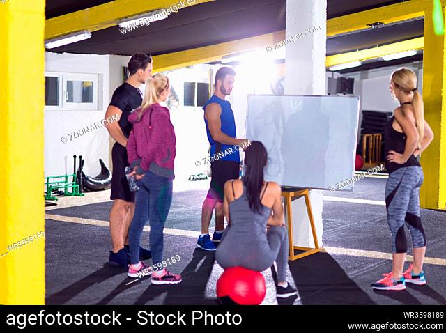 Crossfit training course.group of young athletes getting instructions from trainer before exercise at crossfitness gym