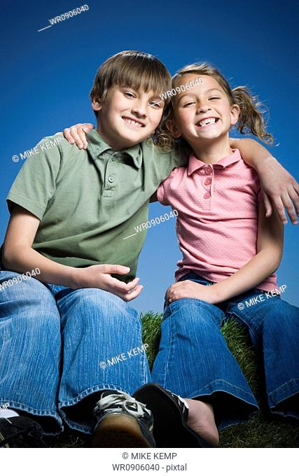 Portrait of a boy sitting with his arm around his sister