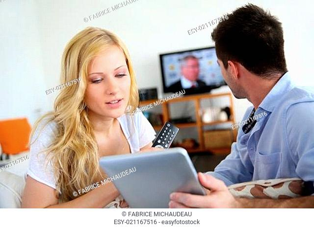 Young couple choosing tv program on internet