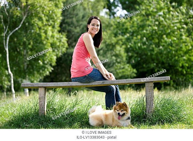 A young woman sitting on a bench, with her dog
