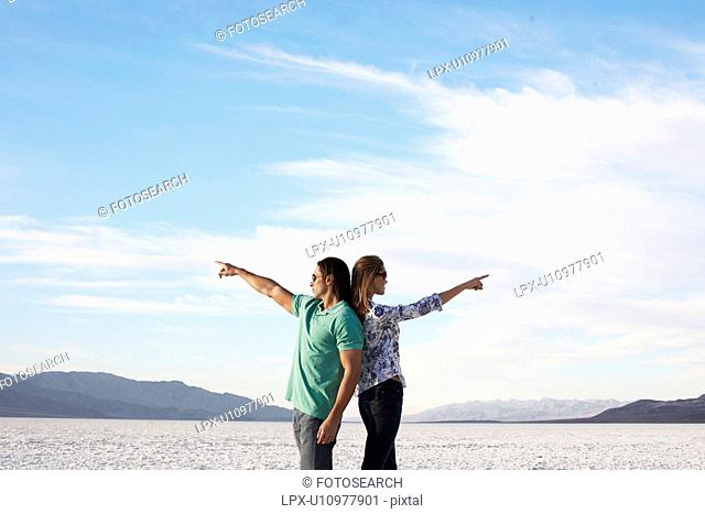 Couple standing back to back and pointing to opposite directions by lake