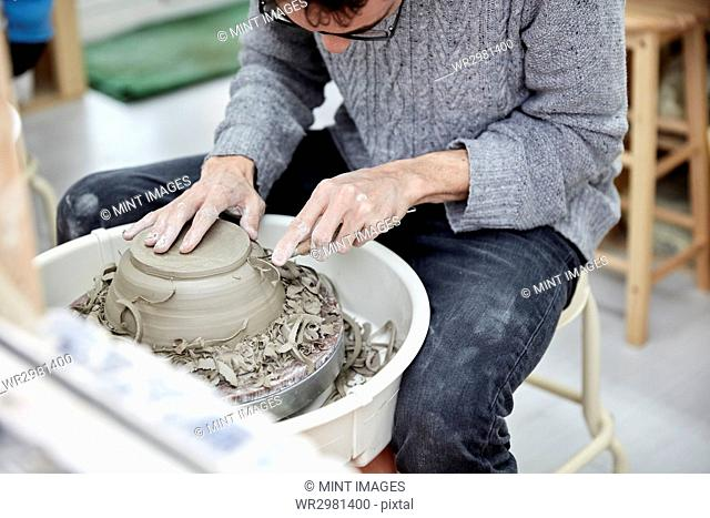 A man using a pottery wheel, shaping a pot base with a small handheld tool shaving off excess clay