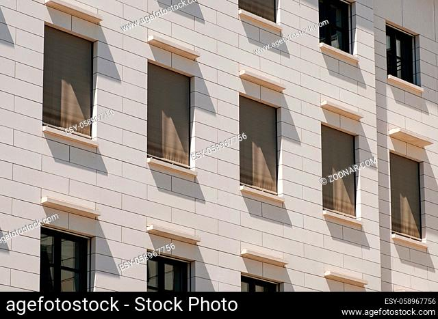 windows building facade with closed shutters / sun blinds -