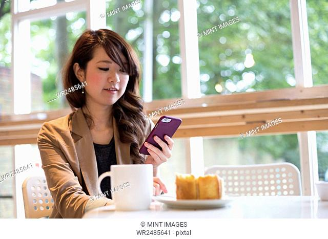 Smiling young woman sitting at a table with a mug and slice of cake, looking at her smart phone
