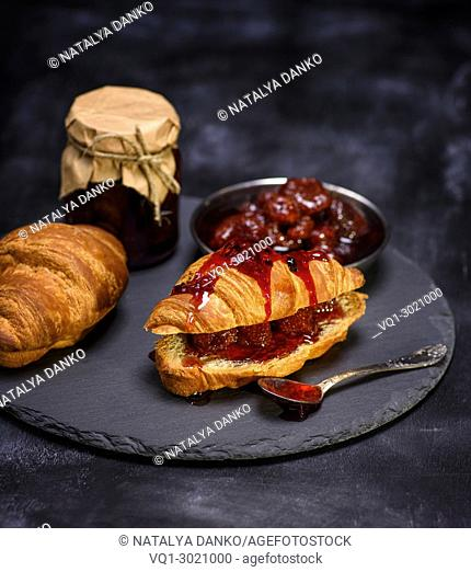 baked croissant with strawberry jam on a black background, close up