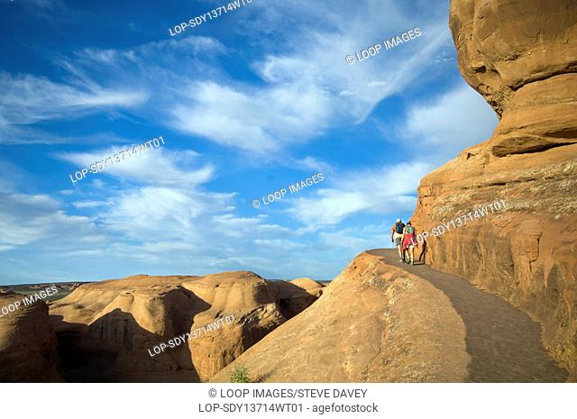 Tourists hiking on a mountain path in Arches National Park