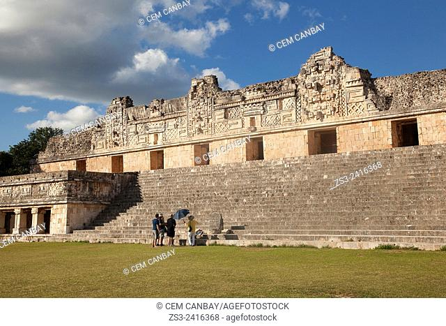 Tourists with a guide and an umbrella in Uxmal Ruins near the Quadrangle Of The Nuns, Yucatan Province, Mexico, Central America