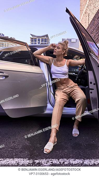 Australia, Adelaide, women fashion blogger and actress Sarah Jeavons posing in car