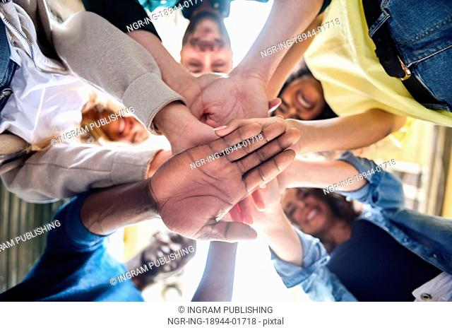 Close up view of young people putting their hands together. Friends with stack of hands showing unity and teamwork