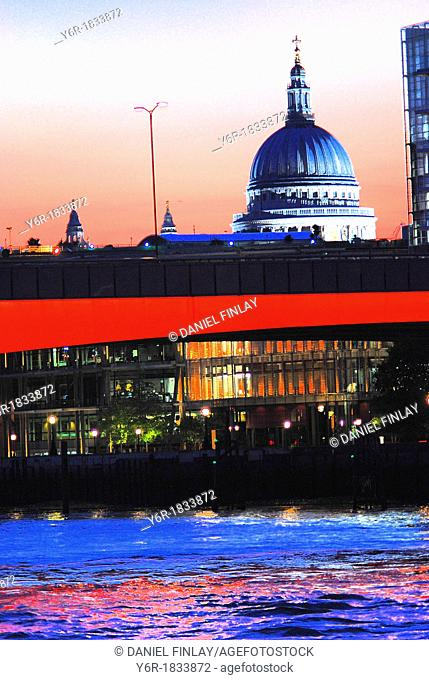View of St  Paul's Cathedral, the illuminated London Bridge and the River Thames at dusk in London, England on a Winter evening  City of London offices glimmer...