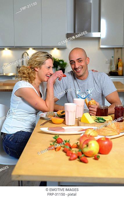 Happy couple having breakfast in kitchen