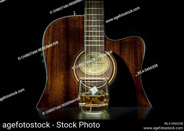 Music concept image, classic guitar with a Whiskey glas on a black background, Jazz, rock, blues music or life style concept