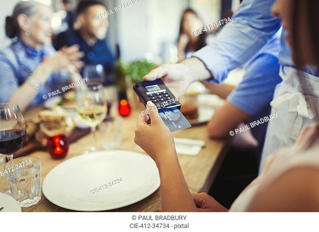 Woman with credit card paying waiter, using credit card reader at restaurant table