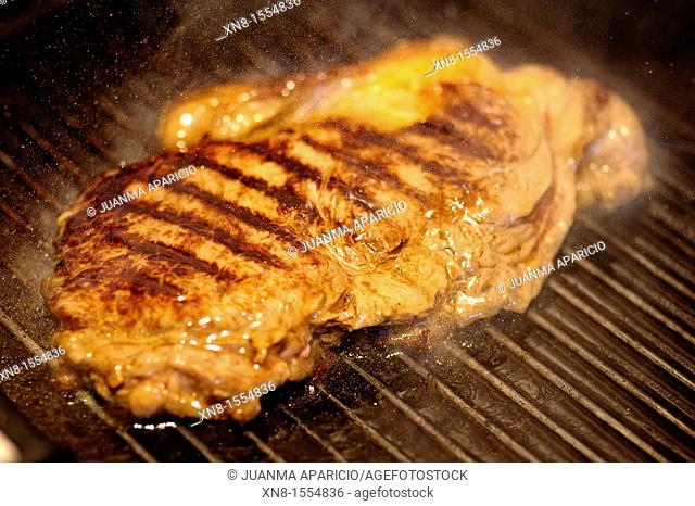 Horizontal image of a steak on the grill