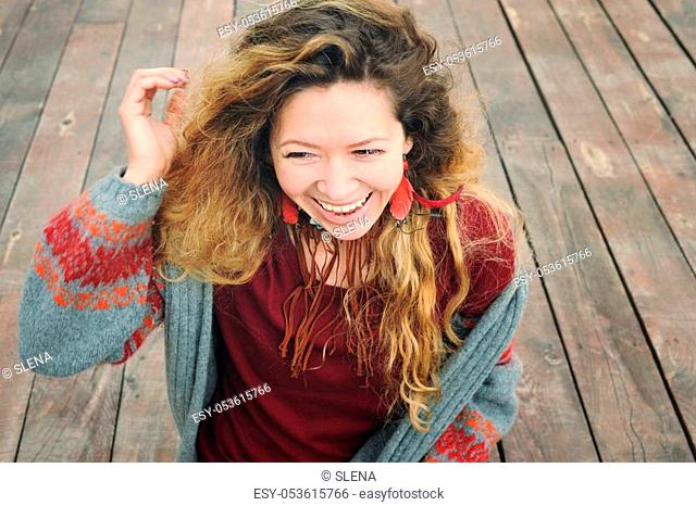 Happy smiling young woman outdoor portrait dressed in gray knitted jersey