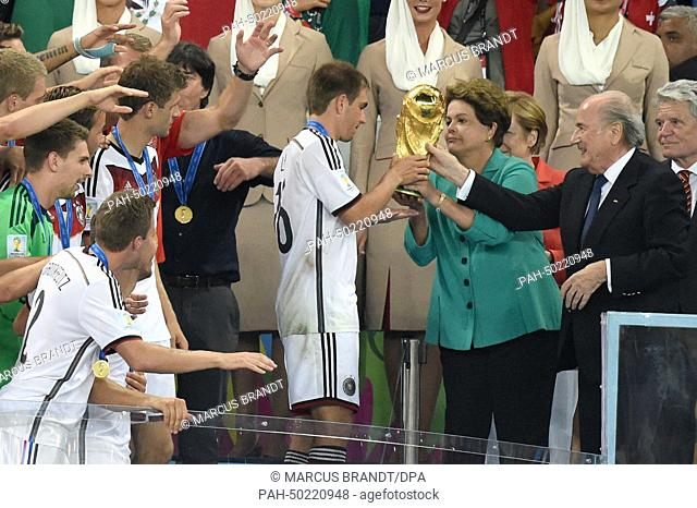 Philipp Lahm (C) of Germany receives the Wolrd Cup trophy from Brazil's President Dilma Rousseff (4-R) next to German Chancellor Angela Merkel (3-R)