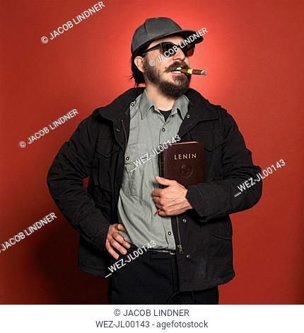 Man with cap, glasses and cigar, holding a Lenin book