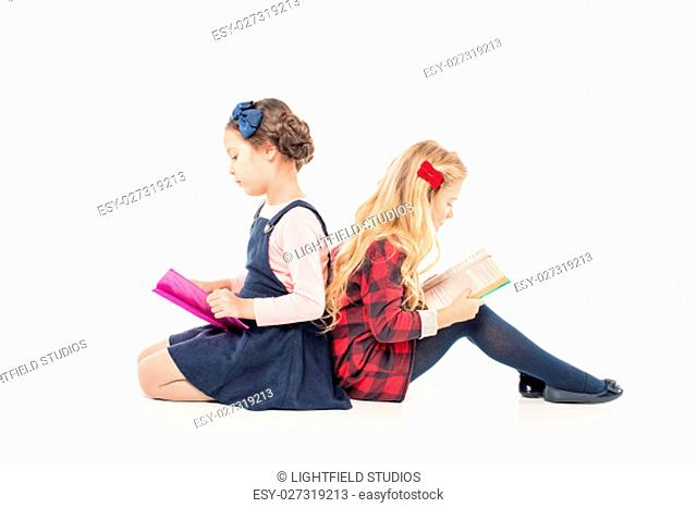 Schoolgirls sitting and reading books on white
