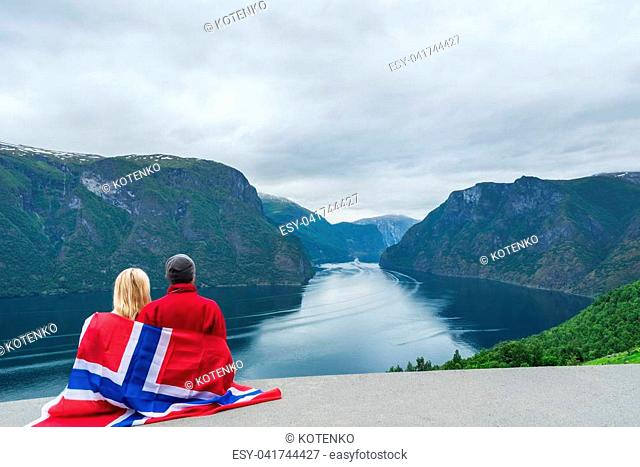 Panorama of Aurlandsfjord. Tourist couple with the flag of Norway enjoys a beautiful view of the fjord and mountains