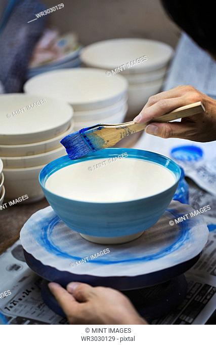 Close up of person working in a Japanese porcelain workshop, painting white bowls with blue glaze