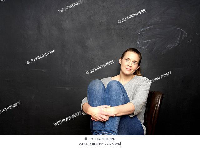 Portrait of smiling woman sitting in front of blackboard