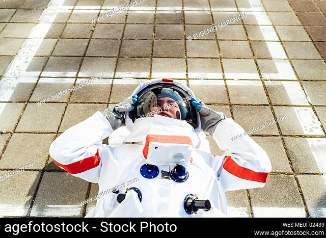 Young female astronaut in space suit lying down on footpath
