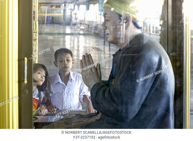 Myanmar (formerly Burma). Yangon (Rangoon). Kyaukhtatgyi Pagoda. Young children in admiration in front of a statue