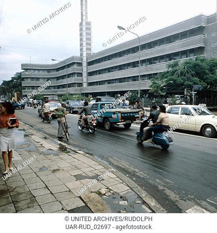 Straßenverkehr vor dem Savoy Homann Hotel in Bandung auf Java, Indonesien 1980er Jahre. Traffic in front of the Savoy Homann Hotel of Bandung on the island of...