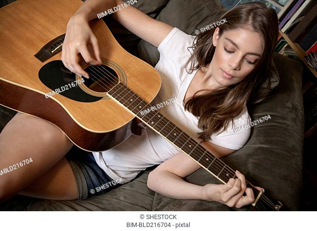 Caucasian woman playing guitar on sofa