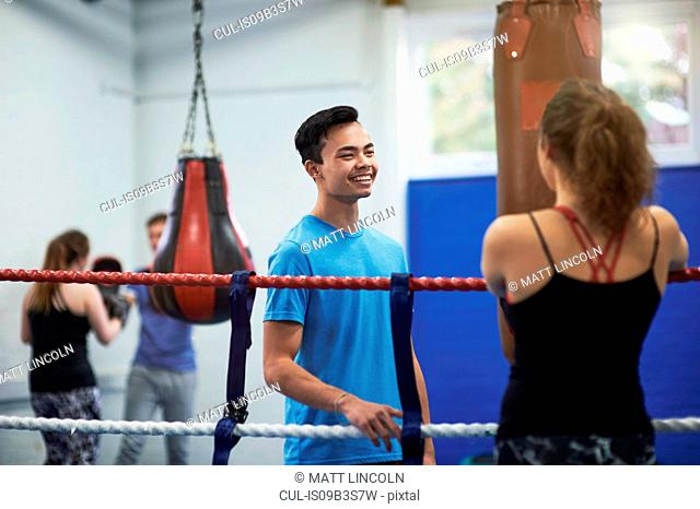Female boxer in boxing ring talking to male boxer