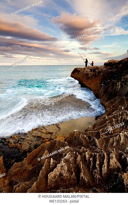 Landscape photo of two men fishing on the rocks. Arniston/Waenhuiskrans, Western Cape, South Africa